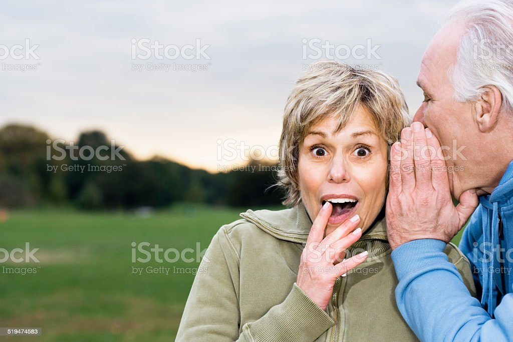 Senior man telling woman secret, outdoors, portrait stock photo