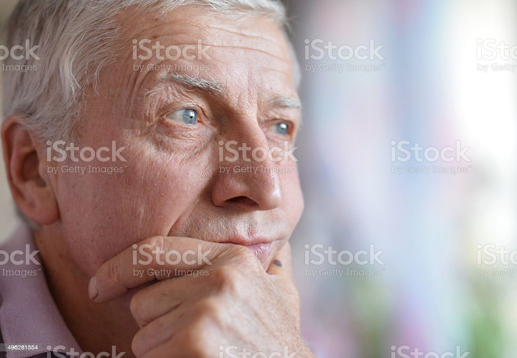 close-up portrait of a senior man thinking about something