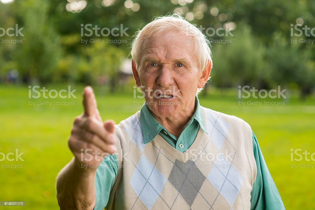 Senior man threatens with finger. stock photo