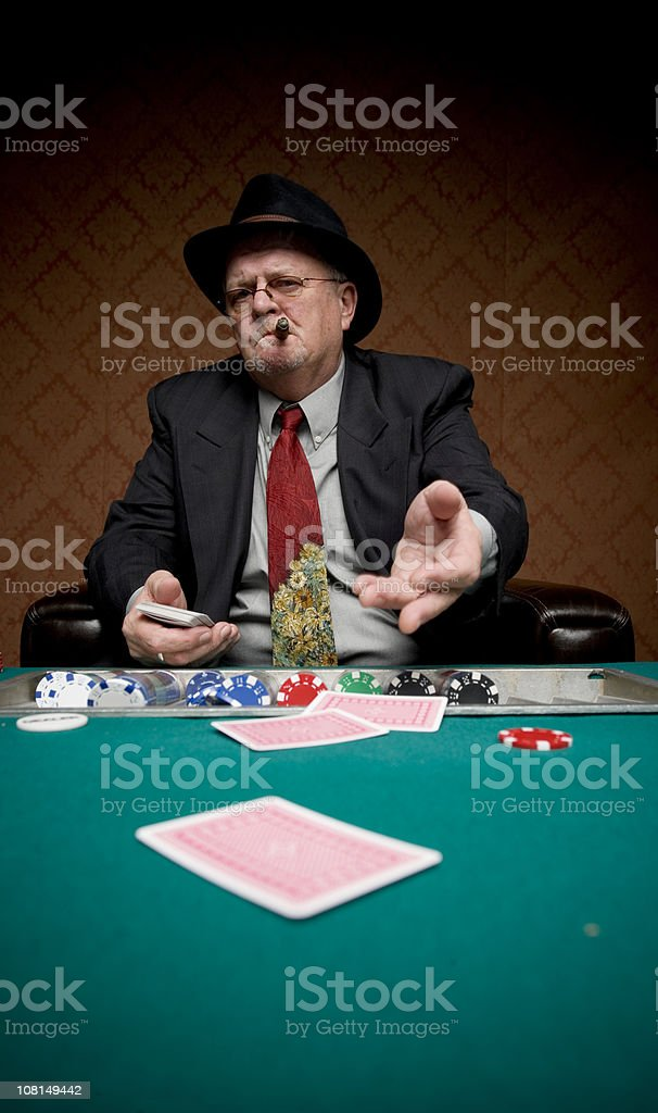 Senior Man Throwing Down His Cards at Poker Table stock photo