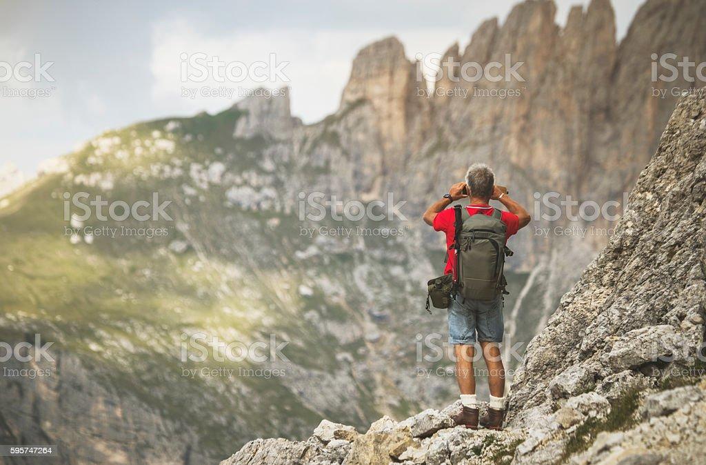 Senior man trail hiking on high mountain stock photo