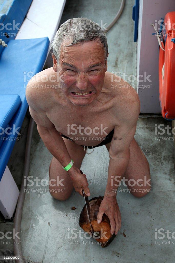 Senior Man tries to open a Coconut stock photo