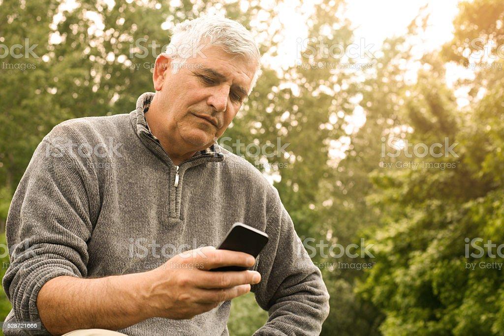 Senior man typing message on fresh air. stock photo