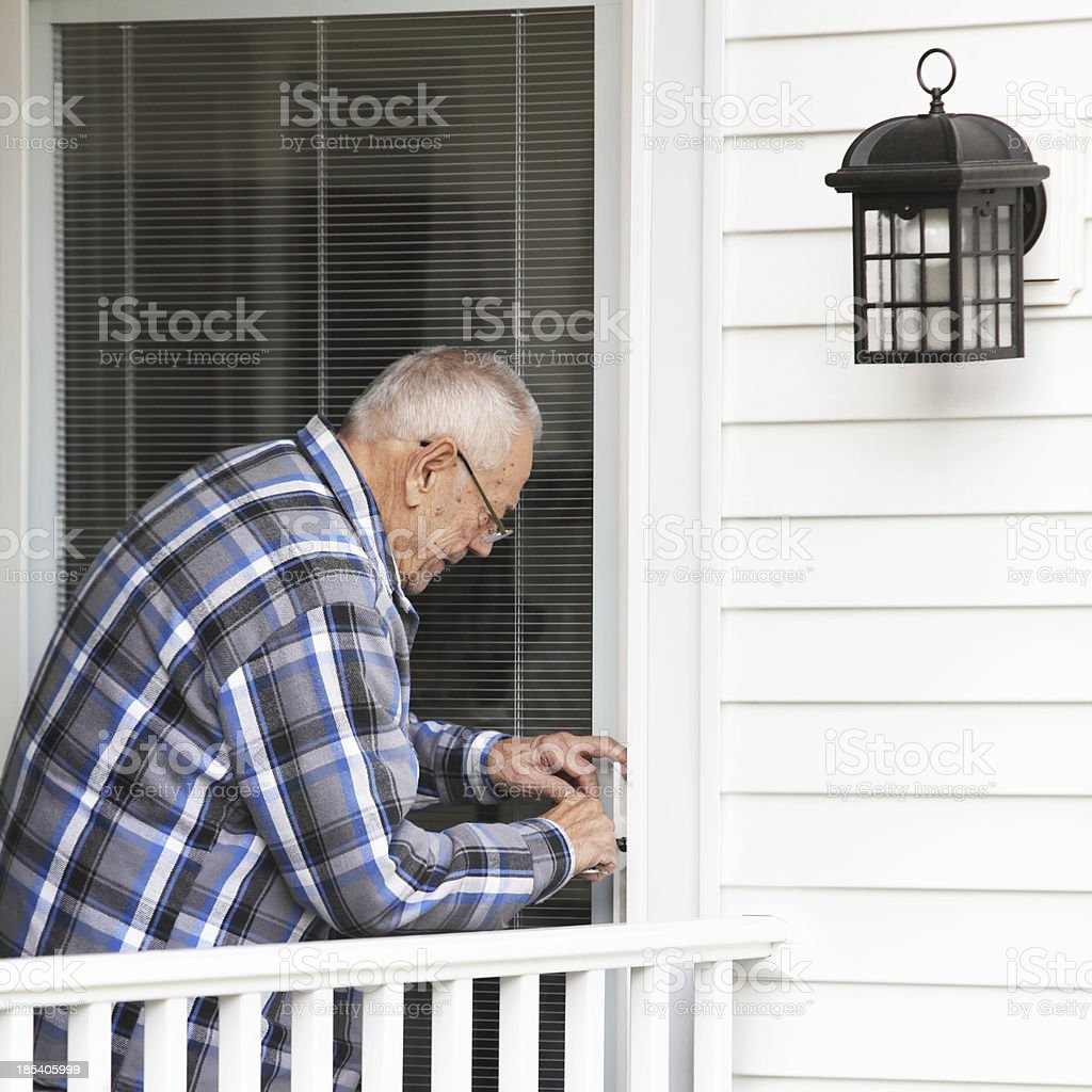 Senior Man Unlocking Front Door royalty-free stock photo