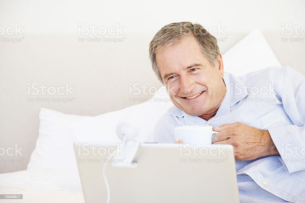 A senior man using a laptop while drinking coffee in bed royalty-free stock photo