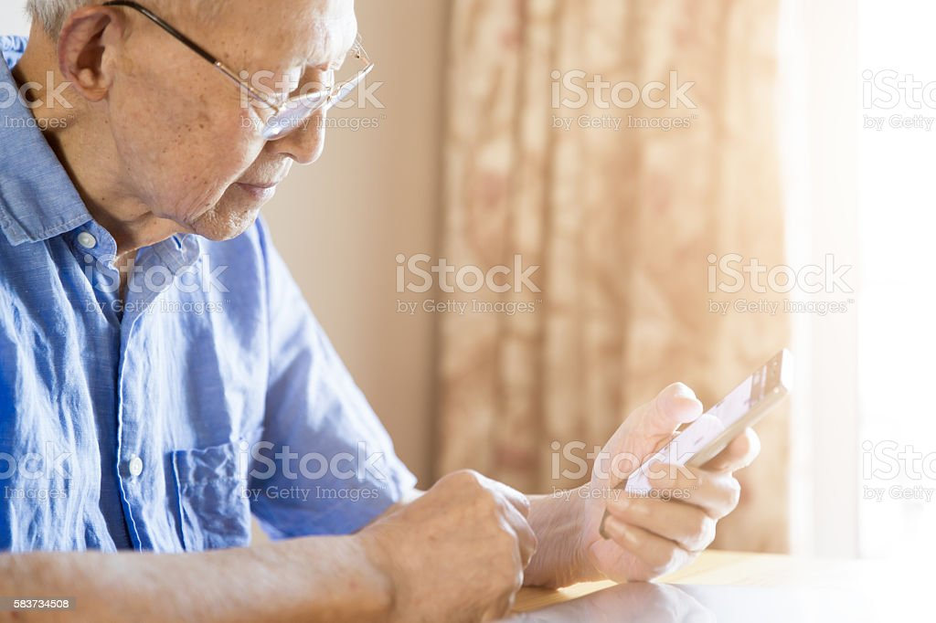 Senior Man Using a Smartphone stock photo