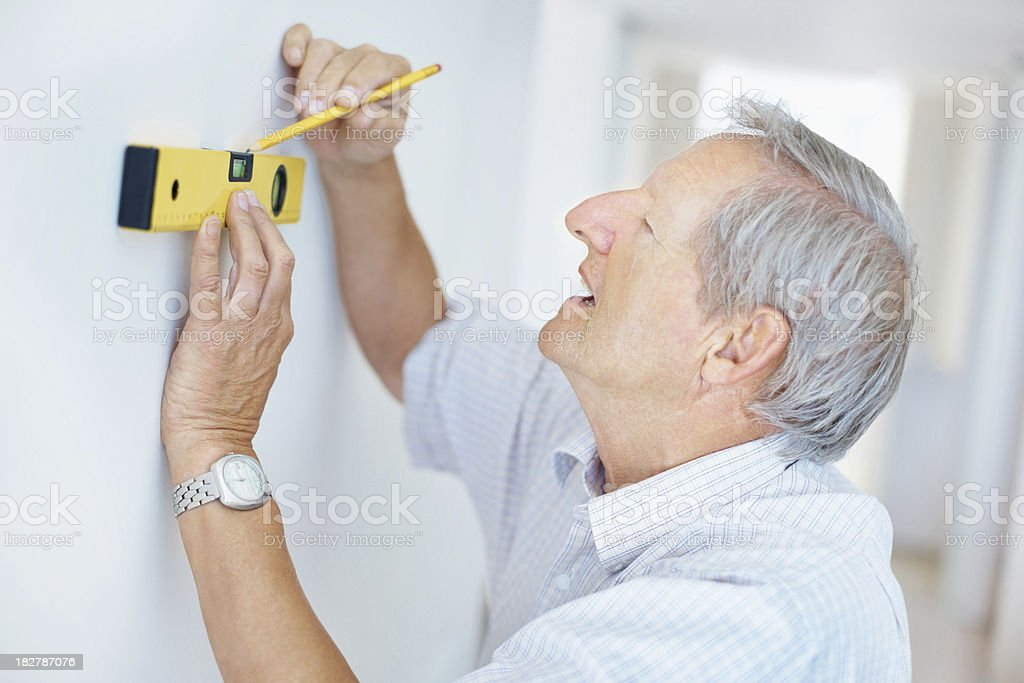 Senior man using a spirit level to make wall markings royalty-free stock photo