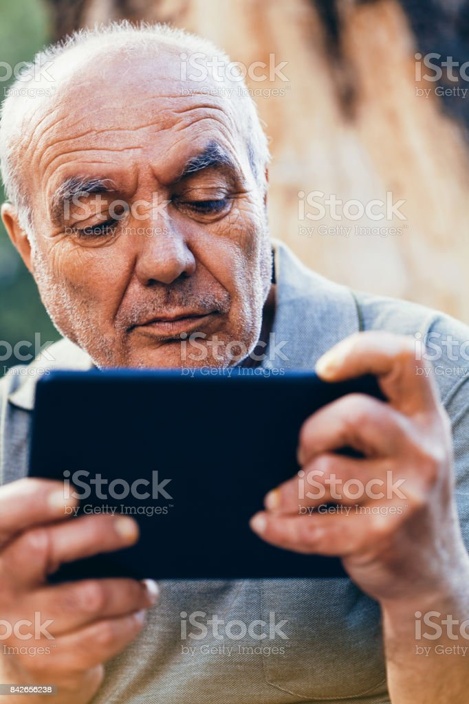 Senior man using a tablet stock photo