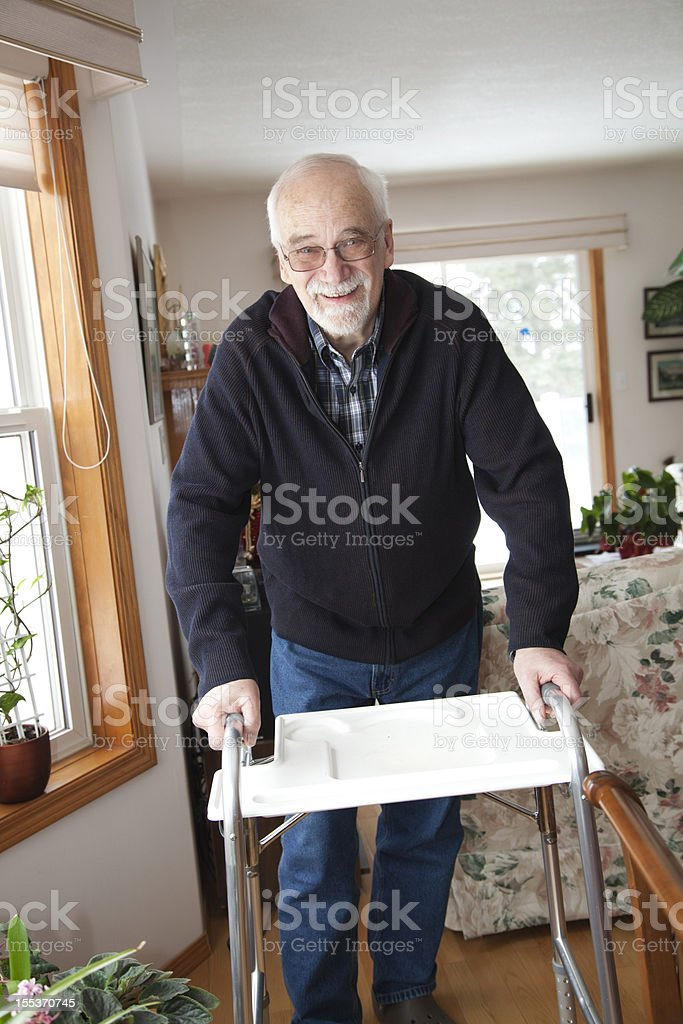 A senior man using a walker in a home stock photo