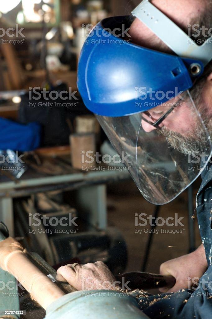 Senior man using a wood lathe in wood shop. stock photo