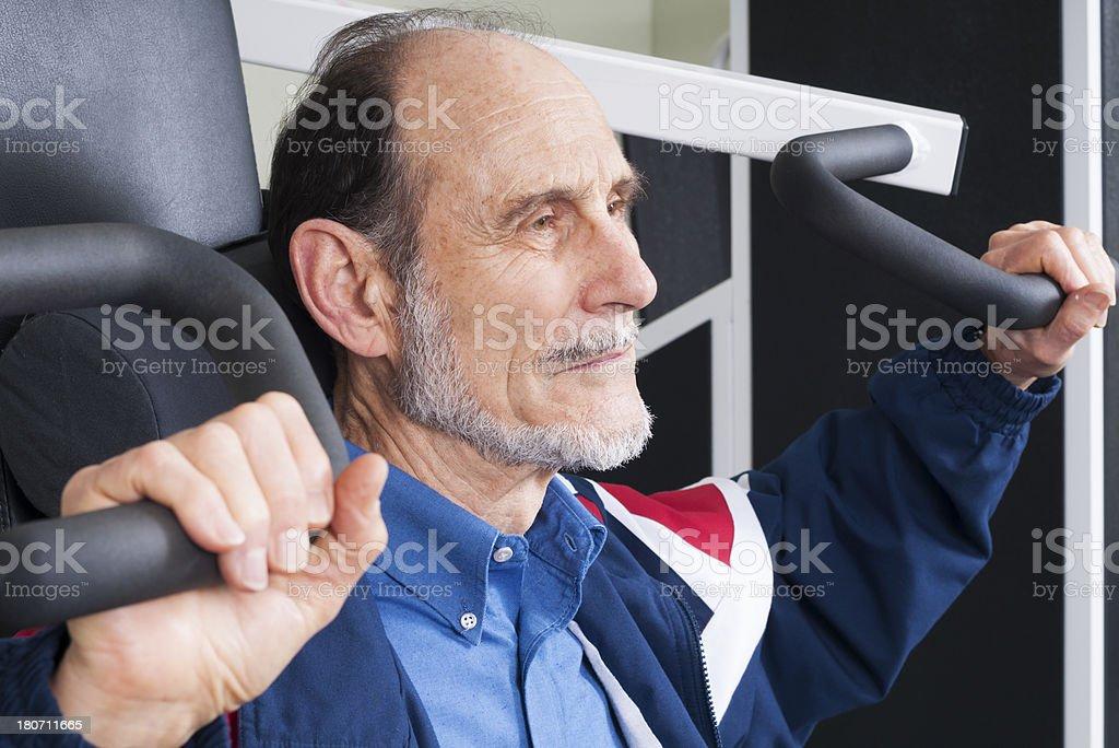 Senior Man Using Arm Weight Machine stock photo