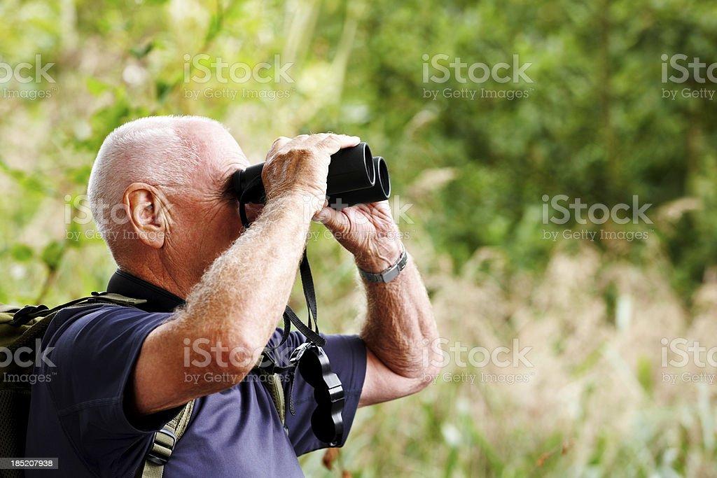 Senior man using binoculars while hiking stock photo