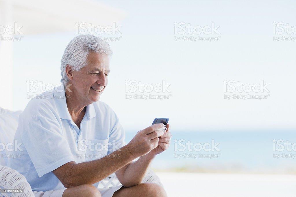 Senior man using cell phone on beach patio stock photo