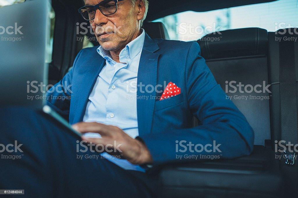 Senior man using computer in taxi stock photo