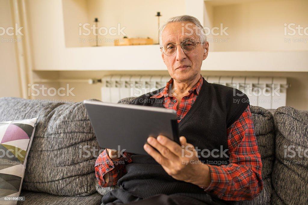 Senior man using digital tablet at home stock photo