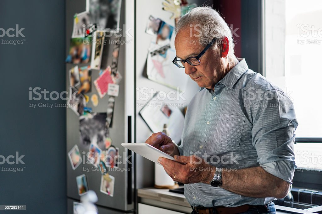 Senior man using digital tablet in kitchen stock photo