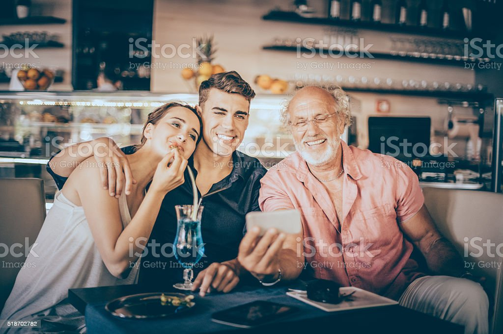 Senior man using digital tablet with teenage couple stock photo