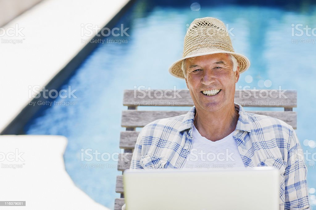 Senior man using laptop at poolside royalty-free stock photo