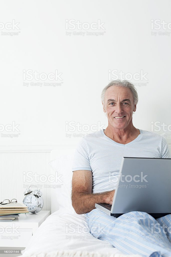 Senior man using laptop in bed. royalty-free stock photo