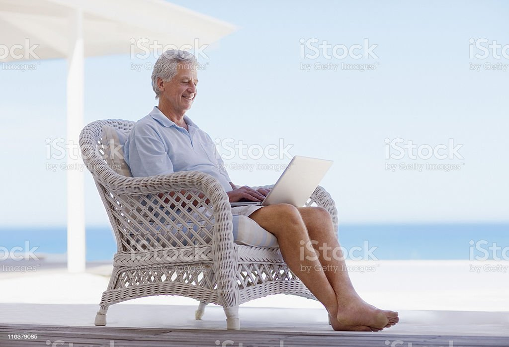Senior man using laptop on beach patio stock photo