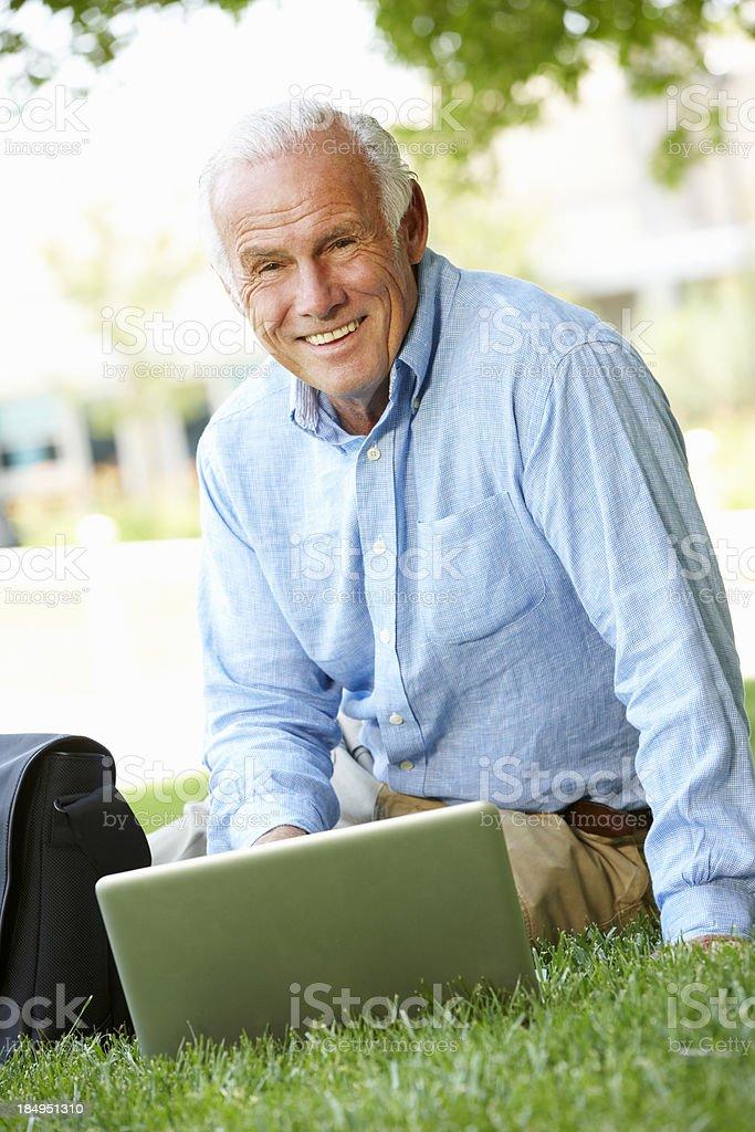 Senior man using laptop outdoors royalty-free stock photo