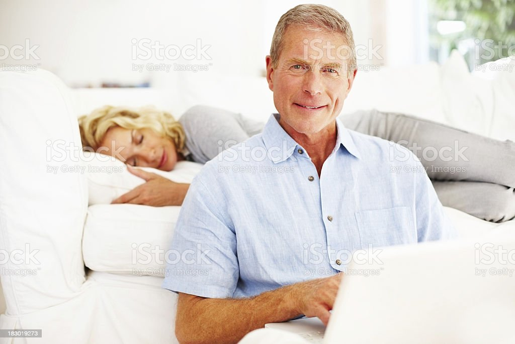 Senior man using laptop with woman sleeping in the background royalty-free stock photo