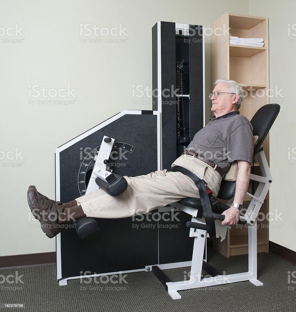 Senior Man Using Leg Exercise Machine - Physical Therapy Series stock photo