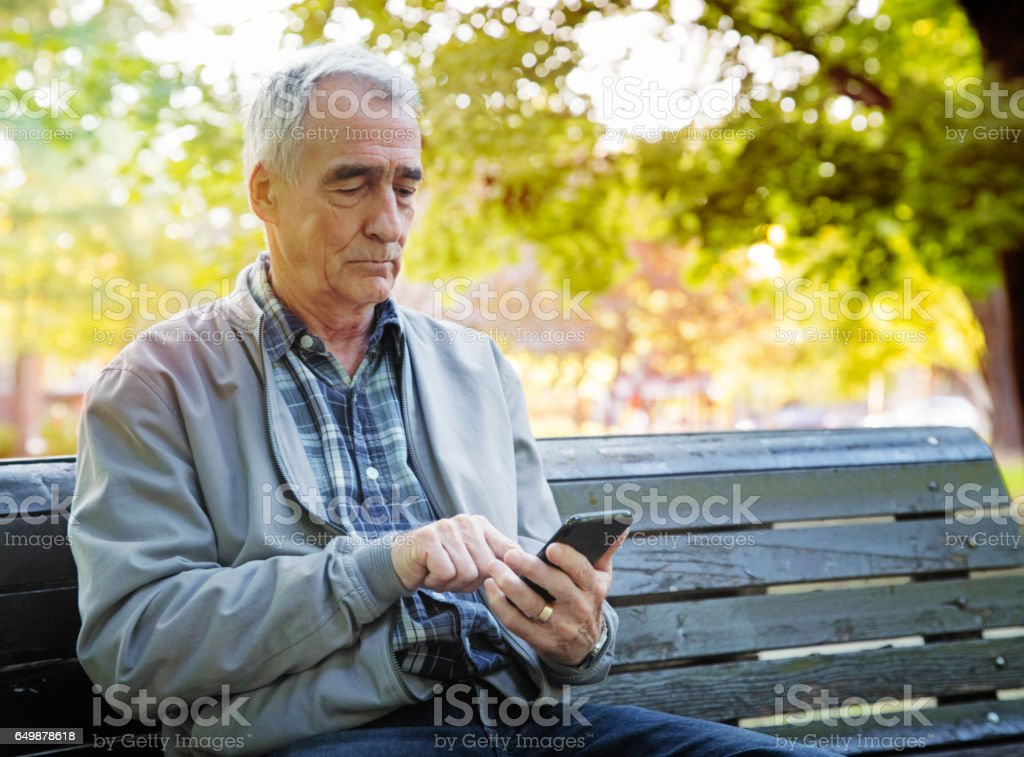 Senior man using mobile phone alone in a public park stock photo