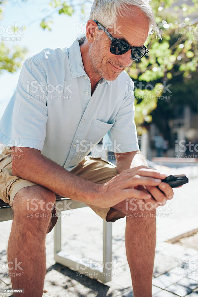 Senior man using mobile phone while sitting outdoors stock photo