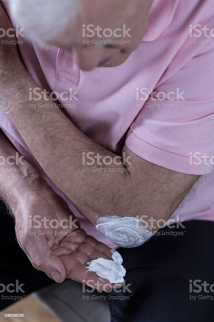 Senior man using ointment stock photo