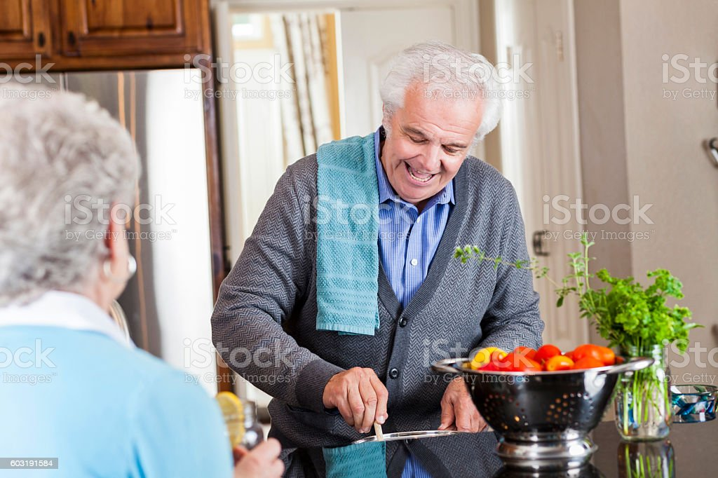 Senior man visits with his wife while he prepares dinner stock photo
