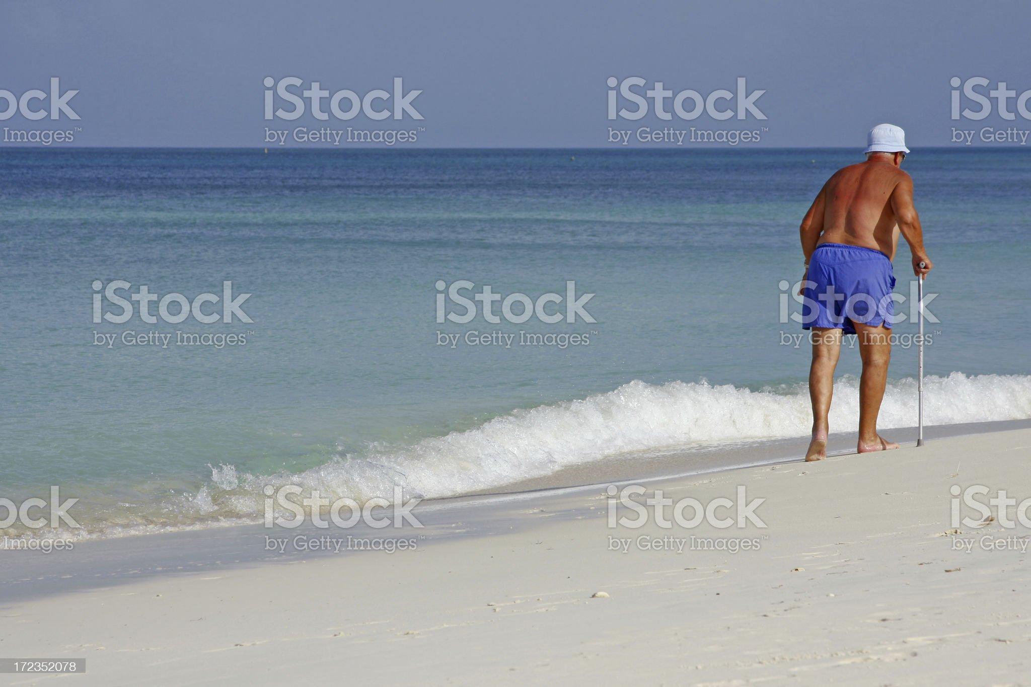 Senior man walking at the beach royalty-free stock photo