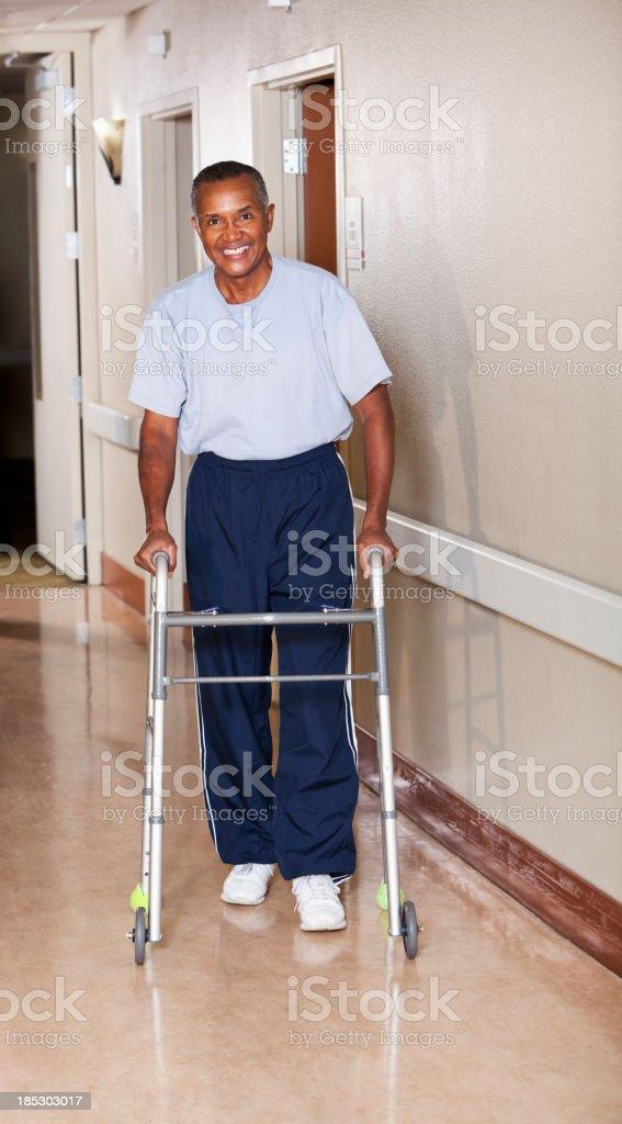 Senior man walking down hospital corridor stock photo