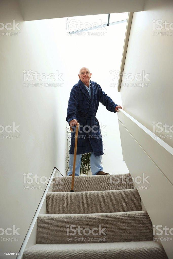 Senior man walking down stairs stock photo