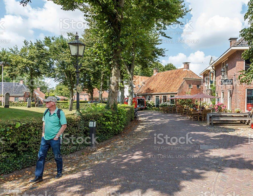 Senior man walking in Nienhove village. stock photo