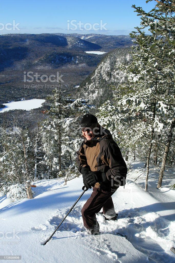 Senior Man Walking in Snowshoe Trail in Winter royalty-free stock photo