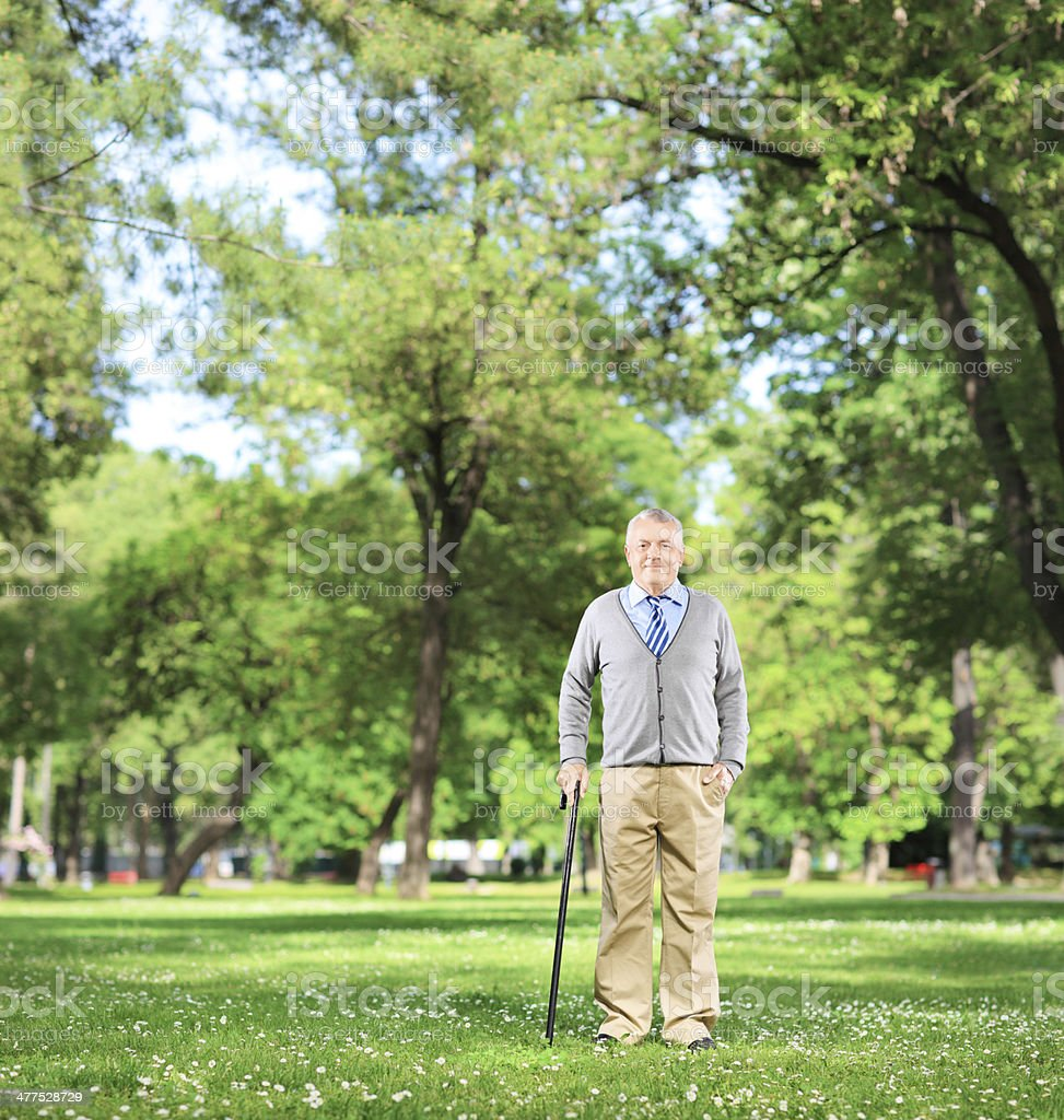 Senior man walking with cane in a park royalty-free stock photo