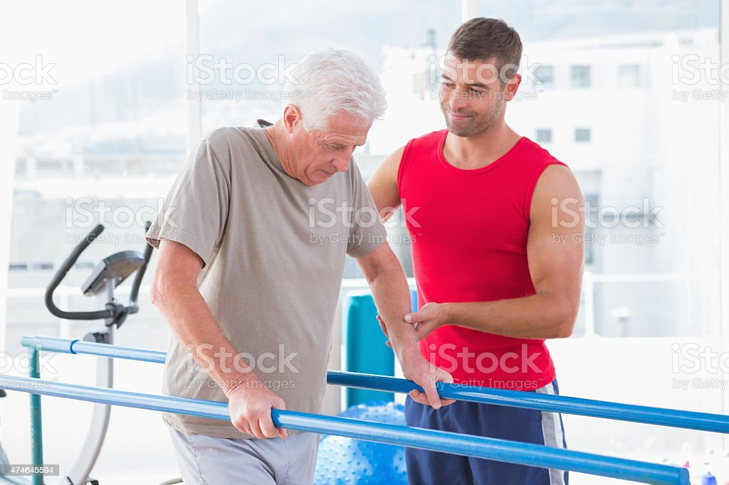 Senior man walking with coach help stock photo
