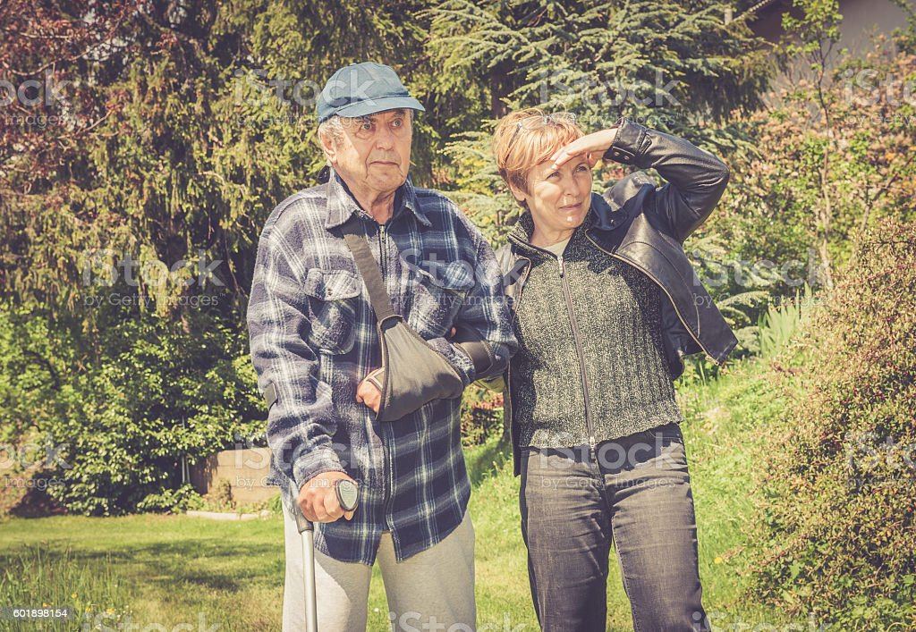 Senior Man walking with Crutch and Helped by his Daughter stock photo