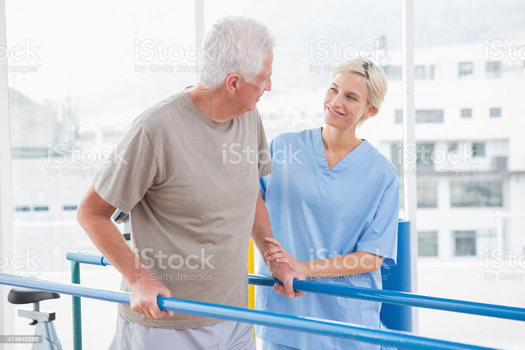 Senior man walking with therapist help stock photo