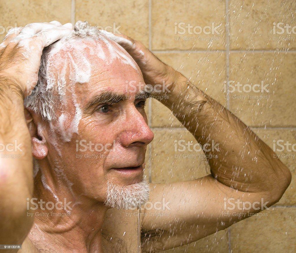 Senior man washing hair in shower royalty-free stock photo