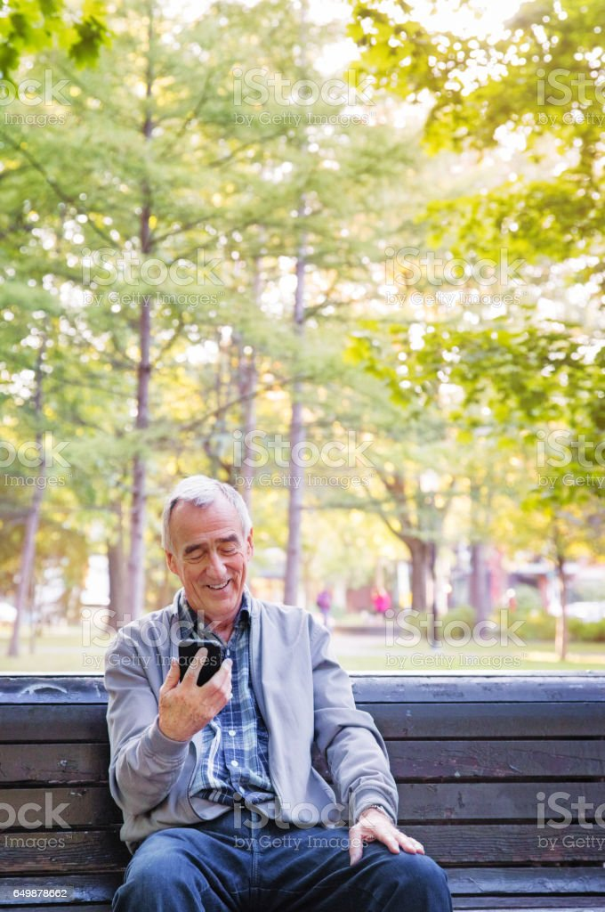 Senior man watching media on mobile phone alone in a public park stock photo