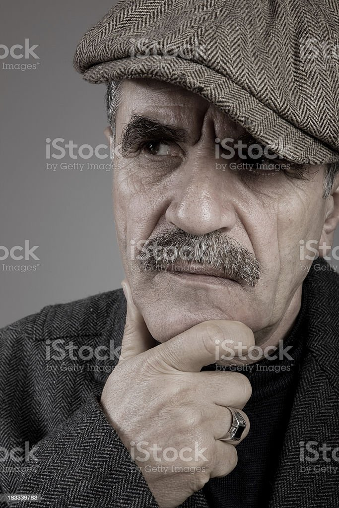 senior man wearing a newsboy cap contemplating and looking aside stock photo