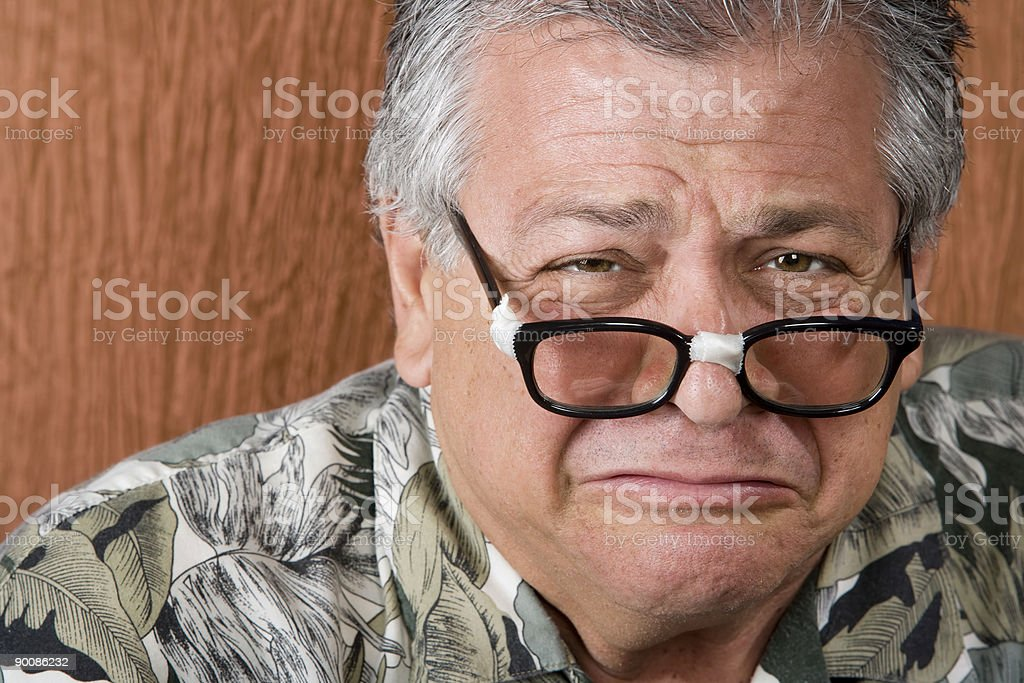 Senior man wearing broken taped glasses over a wooden wall stock photo