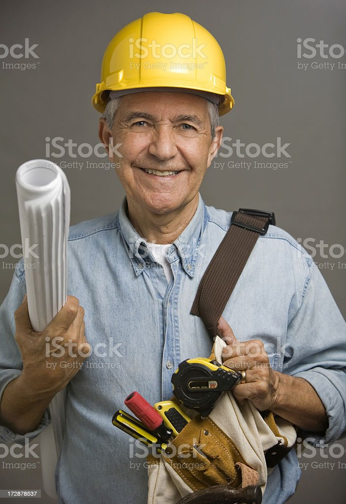 Senior man wearing hard hat and tool belt construction worker royalty-free stock photo