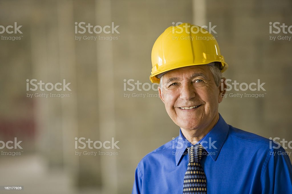 Senior man wearing hard hat at construction site stock photo
