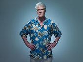 Senior man wearing hawaiian shirt with hands on hips, portrait