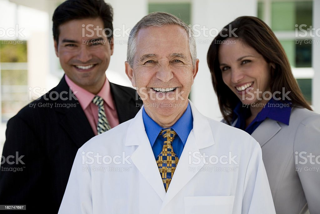 Senior man wearing lab coat with two businesspeople royalty-free stock photo