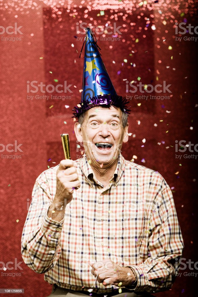 Senior Man Wearing Party Hat With Confetti Above Him royalty-free stock photo