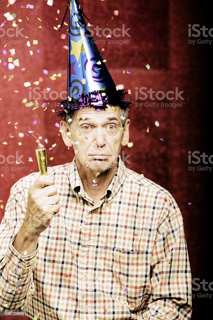 Senior Man Wearing Party Hat With Confetti Above Him stock photo